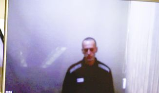 In this photo takes from a video provided by the Babuskinsky District Court on Thursday, April 29, 2021, Russian opposition leader Alexei Navalny is seen on TV screens during a hearing on charges of defamation in the Babuskinsky District Court in Moscow, Russia.  Navalny appeared in court via video link from prison Thursday for an appeal against his conviction and fine for defaming a World War II veteran. Navalny was convicted in February and ordered to pay a fine of 850-thousand rubles (dollars 11,500). (Babuskinsky District Court Press Service via AP)