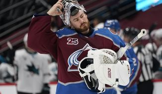 Colorado Avalanche goaltender Philipp Grubauer adjusts his mask as he heads back to the net during a timeout against the San Jose Sharks in the first period of an NHL hockey game Friday, April 30, 2021, in Denver. (AP Photo/David Zalubowski)