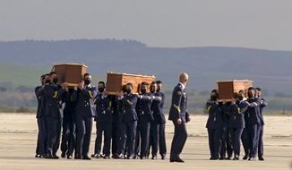 Coffins carrying the bodies of Spanish reporters David Beriain, Roberto Fraile and the director of the Chengeta Wildlife Foundation Rory Young, arrive from Burkina Faso at the Madrid military airport on Friday, April 30, 2021. Two Spanish journalists and the Irish director of a wildlife foundation were killed Monday in an ambush in eastern Burkina Faso. The two journalists were working with the wildlife campaigner on a documentary about poachers in a national park bordering Benin when they were attacked by gunmen. (AP Photo/Andrea Comas)