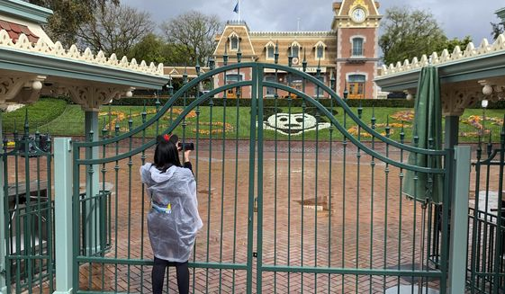 In this March 16, 2020, file photo, a visitor to the Disneyland Resort takes a picture through a locked gate at the entrance to Disneyland in Anaheim, Calif. Disneyland Park and Disney California Adventure park will reopen to visitors on Friday, April 30, 2021. (Jeff Gritchen/The Orange County Register via AP, File)