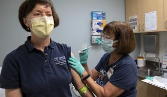 Carol Kelly, left, receives a Moderna variant vaccine shot from registered nurse Mary Bower at Emory University's Hope Clinic, Wednesday afternoon, March 31, 2021, in Decatur, Ga. Kelly was the first person to receive a shot in this new clinical trial. (AP Photo/Ben Gray)