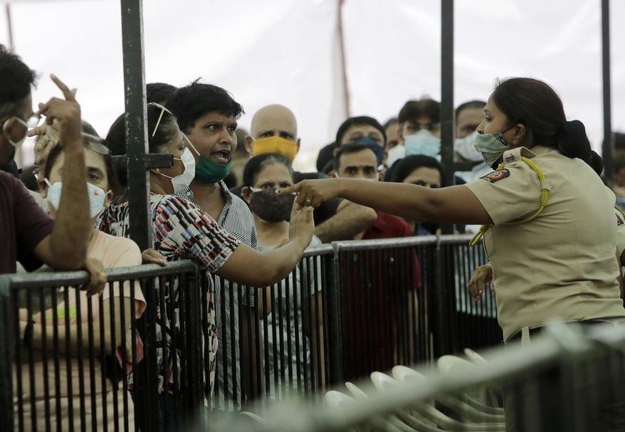 A man argues with a policewoman as he waits with others to receive COVID-19 vaccine outside a vaccination centre in Mumbai, India, Thursday, April 29, 2021. India set another global record in new virus cases Thursday, as millions of people in one state cast votes despite rising infections and the country geared up to open its vaccination rollout to all adults amid snags. (AP Photo/Rajanish Kakade)