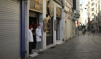 Workers at a pastry shop wait for customers on a virtually deserted Istiklal Street, the main shopping street of Istanbul, Friday, April 30, 2021, on the first day of a tight lockdown to help protect from the spread of the coronavirus. Turkish security forces on Friday patrolled main streets and set up checkpoints at entry and exits points of cities, to enforce Turkey's strictest COVID-19 lockdown to date. Still, many people were on the move as the government, desperate not to shut down the economy completely, kept some sectors exempt from the restrictions. (AP Photo/Emrah Gurel)