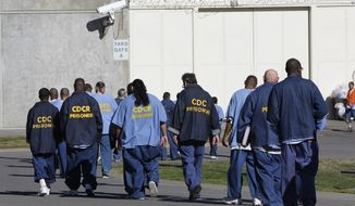 In this Feb. 26, 2013, file photo, inmates walk through the exercise yard at California State Prison Sacramento, near Folsom, Calif. California is giving 76,000 inmates, including violent and repeat felons, the opportunity to leave prison earlier as the state aims to further trim the population of what once was the nation's largest state correctional system. The new rules take effect Saturday, May 1, 2021, but it will be months or years before any inmates go free earlier.   (AP Photo/Rich Pedroncelli, File)