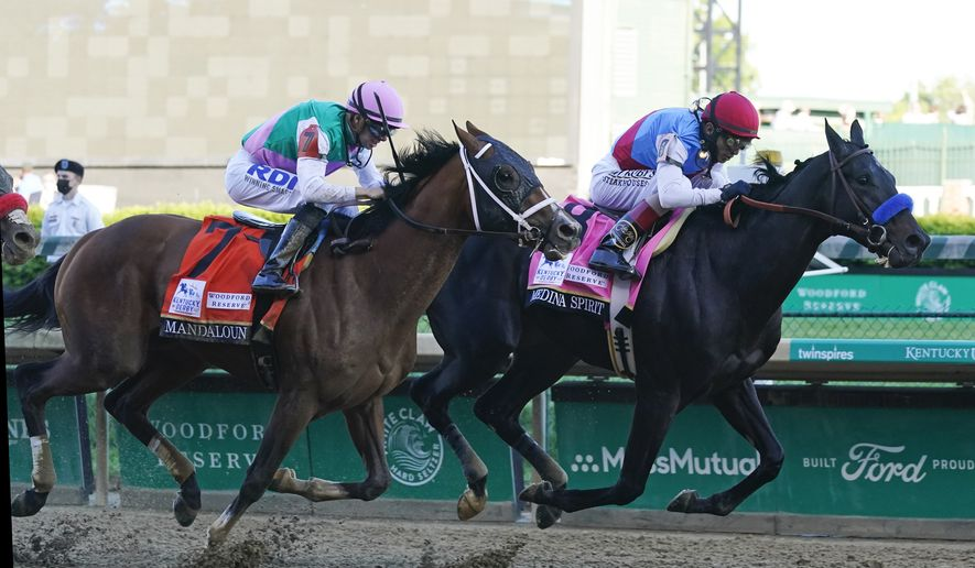 John Valazquez, right, rides Medina Spirit ahead of Florent Geroux aboard Mandaloun to win the 147th running of the Kentucky Derby at Churchill Downs, Saturday, May 1, 2021, in Louisville, Ky. (AP Photo/Darron Cummings)