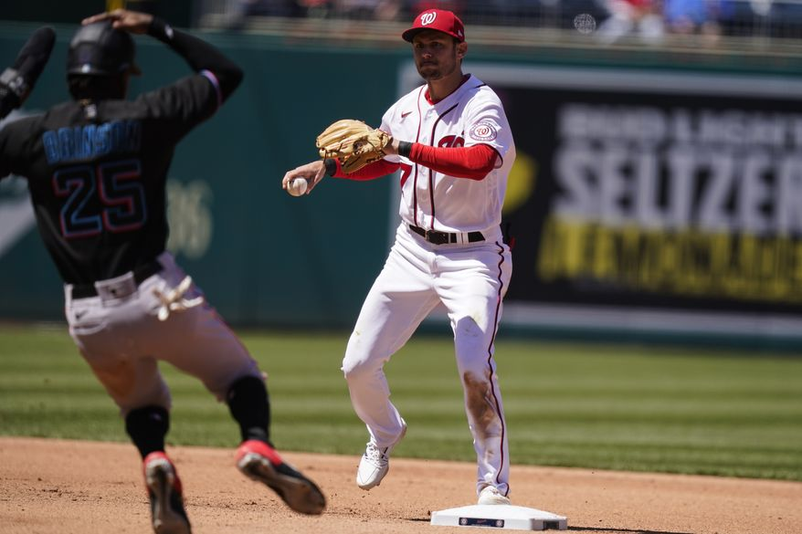Washington Nationals shortstop Trea Turner (7) forces the out on Miami Marlins' Lewis Brinson at second before throwing to first base for a double play during the fourth inning of a baseball game at Nationals Park, Saturday, May 1, 2021, in Washington. (AP Photo/Alex Brandon)