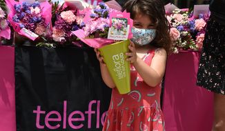 """IMAGE DISTRIBUTED FOR TELEFLORA - A young girl grabs a Teleflora bouquet to share with Mom in advance of Mother's Day as part of Teleflora's Mother's Day sidewalk chalk activation at Santa Monica Place on Saturday, May 1, 2021, in Santa Monica, Calif. An extension of its Mother's Day campaign, """"Drawn to Mom,"""" Teleflora, the world's leading floral delivery company, is highlighting what the past year has been like from a child's perspective, and the joy of having mom right there through it all. (Jordan Strauss/AP Images for Teleflora)"""