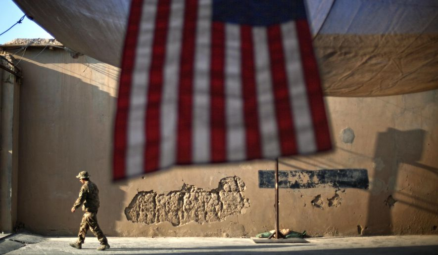 """In this Sept. 11, 2011, file photo, a U.S. Army soldier walks past an American flag hanging in preparation for a ceremony commemorating the 10th anniversary of the 9/11 attacks, at Forward Operating Base Bostick in Kunar province, Afghanistan. The final phase of ending America's """"forever war"""" in Afghanistan after 20 years formally began Saturday, May 1, 2021, with the withdrawal of the last U.S. and NATO troops by the end of summer. (AP Photo/David Goldman, File)"""