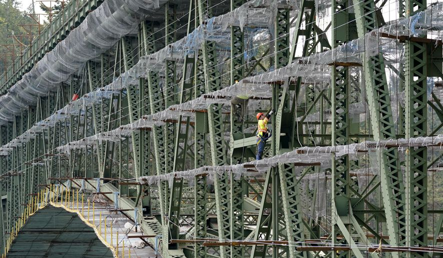 A worker stands on scaffolding attached to the Deception Pass Bridge, a 976-foot span about 180-feet above the waters below, as work to replace corroded steel and paint the structure continues Thursday, April 29, 2021, in Deception Pass, Wash. The 86-year old bridge, along with its 511-foot long companion Canoe Pass Bridge, spanning immediately to the north, connect Whidbey Island on the south to Fidalgo Island. (AP Photo/Elaine Thompson) ** FILE **