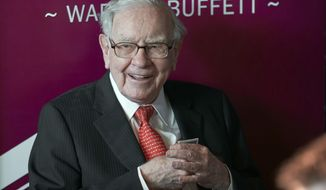 FILE - In this May 5, 2019, file photo Warren Buffett, Chairman and CEO of Berkshire Hathaway, smiles as he plays bridge following the annual Berkshire Hathaway shareholders meeting in Omaha, Neb.  Buffett will spend Saturday afternoon fielding questions at Berkshire Hathaway's annual meeting, which is being held virtually.  (AP Photo/Nati Harnik, File)