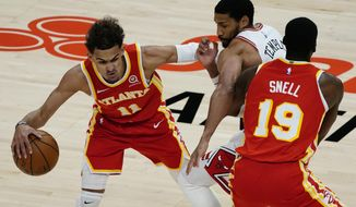 Chicago Bulls forward Garrett Temple (17) tries to get around a screen set by Atlanta Hawks forward Tony Snell (19) as he covers Hawks' Trae Young (11) in the first half of an NBA basketball game Saturday, May 1, 2021, in Atlanta. (AP Photo/John Bazemore)