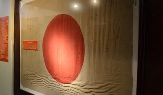 In this August 10, 2020, photo provided by Amy E. Tuschen and The Augusta Chronicle, Signal Corps personnel captured this Japanese flag from a communications outpost during the Battle of Okinawa in 1945, near the end of World War II, now on display at the Fort Gordon Historical Museum, in Fort Gordon, Ga. (Amy E. Tuschen/Fort Gordon Historical Museum Society via AP)