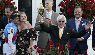 Jockey John Velazquez, left, watches as trainer Bob Baffert holds up the winner's trophy after they victory with Medina Spirit in the 147th running of the Kentucky Derby at Churchill Downs, Saturday, May 1, 2021, in Louisville, Ky. (AP Photo/Jeff Roberson) ** FILE **