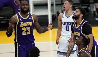 Sacramento Kings guard Tyrese Haliburton (0) reacts after scoring, between Los Angeles Lakers forwards LeBron James (23) and Anthony Davis, right, during the second half of an NBA basketball game Friday, April 30, 2021, in Los Angeles. (AP Photo/Marcio Jose Sanchez)