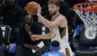 Indiana Pacers forward Domantas Sabonis (11) passes in front of Oklahoma City Thunder forward Darius Bazley (7) in the second half of an NBA basketball game Saturday, May 1, 2021, in Oklahoma City. (AP Photo/Sue Ogrocki)
