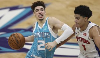 Charlotte Hornets guard LaMelo Ball, left, drives against Detroit Pistons guard Killian Hayes in the second half of an NBA basketball game in Charlotte, N.C., Saturday, May 1, 2021.  (AP Photo/Nell Redmond)
