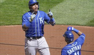 Kansas City Royals Salvador Perez, left, and Carlos Santana celebrate a two-run home run by Perez in the third inning of a baseball game Saturday, May 1, 2021, in Minneapolis. (AP Photo/Jim Mone)