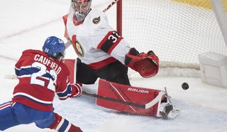 Montreal Canadiens' Cole Caufield scores against Ottawa Senators' goaltender Filip Gustavsson during overtime of an NHL hockey game in Montreal, Saturday, May 1, 2021. (Graham Hughes/The Canadian Press via AP)