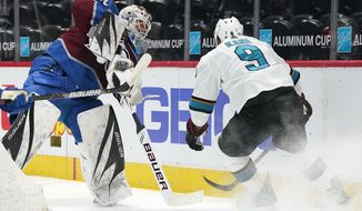 Colorado Avalanche goaltender Devan Dubnyk, left, clears the puck as San Jose Sharks left wing Evander Kane pursues in the first period of an NHL hockey game Saturday, May 1, 2021, in Denver. (AP Photo/David Zalubowski)