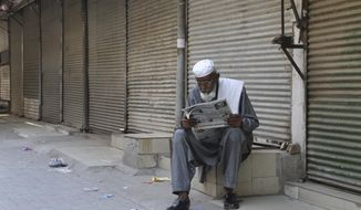 A man reads a morning newspaper at a market closed due to new restrictions announced by government to control the spread of the coronavirus, in Peshawar, Pakistan, Saturday, May 1, 2021. (AP Photo/Muhammad Sajjad)