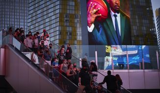 People ride an escalator along the Las Vegas Strip, Saturday, April 24, 2021, in Las Vegas. Las Vegas is bouncing back to pre-coronavirus pandemic levels, with increases in airport passengers and tourism. (AP Photo/John Locher)