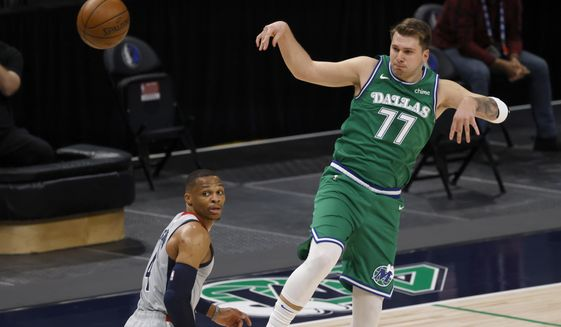 Dallas Mavericks guard Luka Doncic (77) passes the ball over Washington Wizards guard Russell Westbrook (4) during the first half of an NBA basketball game Saturday, May 1, 2021, in Dallas. (AP Photo/Ron Jenkins)