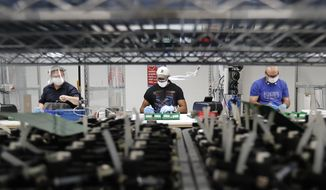 Ford Motor Co., line workers put together ventilators that the automaker is assembling at the Ford Rawsonville plant in Ypsilanti Township, Mich. U.S. Regulations are likely to fall heaviest on the agriculture and manufacturing sectors, which combined account for 33% of all U.S. greenhouse gas emissions. (AP Photo/Carlos Osorio, File)