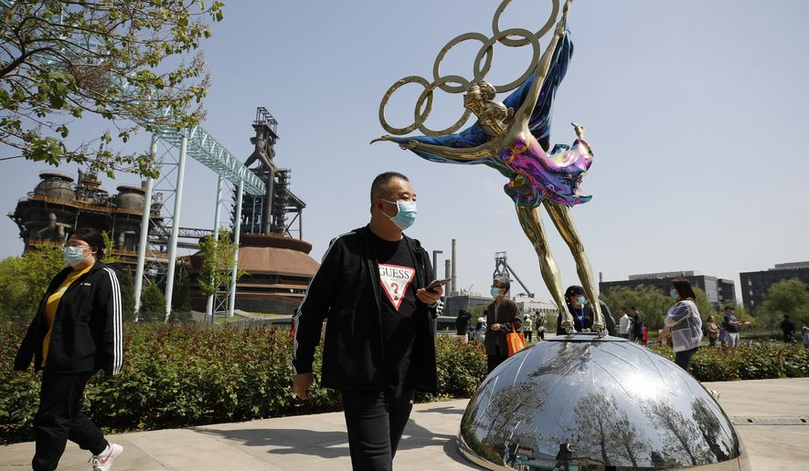 Visitors wearing face masks to help curb the spread of the coronavirus walk by a statue featuring Winter Olympics figure skating on display at the Shougang Park in Beijing, Sunday, May 2, 2021. Chinese tourists are expected to make a total of 18.3 million railway passenger trips on the first day of the country's five-day holiday for international labor day, according to an estimate by the state railway group, as tourists rush to travel domestically after the coronavirus has been brought under control in China. (AP Photo/Andy Wong)