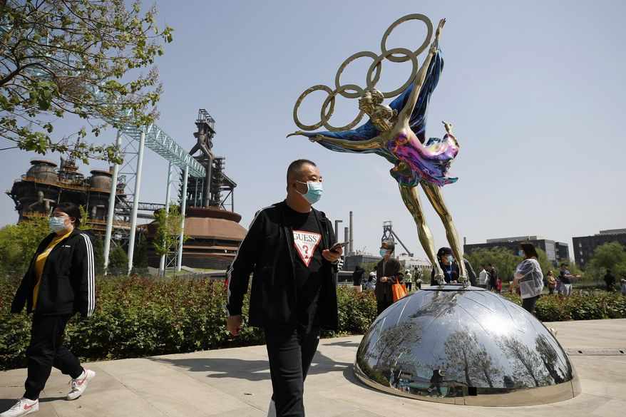 Visitors wearing face masks to help curb the spread of the coronavirus walk by a statue featuring Winter Olympics figure skating on display at the Shougang Park in Beijing, Sunday, May 2, 2021. (AP Photo/Andy Wong) ** FILE **