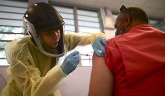In this March 10, 2021, file photo, a health care worker injects a man with a dose of the Moderna COVID-19 vaccine during a mass vaccination campaign, at the Maria Simmons elementary school in Vieques, Puerto Rico. (AP Photo/Carlos Giusti, File)