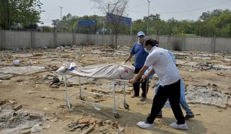 Body of a COVID-19 victim is wheeled in a ground that has been converted into a crematorium in New Delhi, India, Saturday, May 1, 2021. India on Saturday set yet another daily global record with 401,993 new cases, taking its tally to more than 19.1 million. Another 3,523 people died in the past 24 hours, raising the overall fatalities to 211,853, according to the Health Ministry. Experts believe both figures are an undercount. (AP Photo/Amit Sharma)