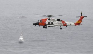 A U.S. Coast Guard helicopter flies over boats searching the area where a boat capsized just off the San Diego coast Sunday, May 2, 2021, in San Diego. (AP Photo/Denis Poroy)