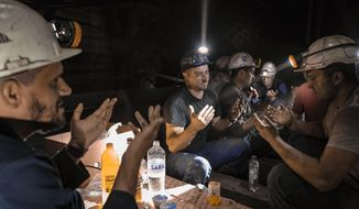 Bosnian coal miners pray after breaking fast in the underground at a mine in Zenica, Bosnia, Thursday, April 29, 2021. Inside mine shafts, one can't see sunset, but miners consult their watches and smartphones for the right time to sit down, unwrap their food and break their daily fast together. (AP Photo/Kemal Softic)