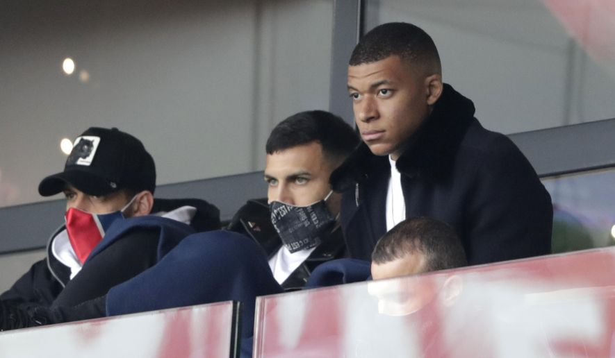 PSG's Kylian Mbappe, right, attends the French League One soccer match between Paris Saint-Germain and Lens at the Parc des Princes stadium in Paris, France, Saturday, May 1, 2021. (AP Photo/Thibault Camus)