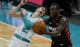 Miami Heat guard Kendrick Nunn, right, pulls a pass away from Charlotte Hornets guard LaMelo Ball during the first half of an NBA basketball game on Sunday, May 2, 2021, in Charlotte, N.C. (AP Photo/Chris Carlson)
