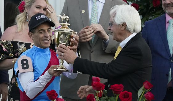 Trainer Bob Baffert hands the winner's trophy to jockey John Velazquez after they victory with Medina Spirit in the 147th running of the Kentucky Derby at Churchill Downs, Saturday, May 1, 2021, in Louisville, Ky. (AP Photo/Jeff Roberson) **FILE**