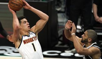 Denver Nuggets forward Michael Porter Jr., left, shoots as Los Angeles Clippers forward Nicolas Batum defends during the first half of an NBA basketball game Saturday, May 1, 2021, in Los Angeles. (AP Photo/Mark J. Terrill)