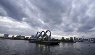 This April 12, 2021, file photo shows the Olympic rings floating in the water in the Odaiba section in Tokyo.  (AP Photo/Eugene Hoshiko, File)  **FILE**
