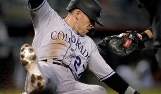 Colorado Rockies' Trevor Story (27) slides safely around the glove of Arizona Diamondbacks catcher Carson Kelly on a base hit by Ryan McMahon during the first inning of a baseball game, Saturday, May 1, 2021, in Phoenix. (AP Photo/Matt York)
