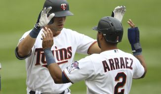 Minnesota Twins' Alex Kirilloff, left, high-fives teammate Luis Arraez (2) after hitting a home run in the eighth inning of a baseball game against the Kansas City Royals, Sunday, May 2, 2021, in Minneapolis. (AP Photo/Stacy Bengs)