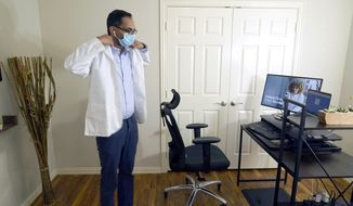 Medical director of Doctor on Demand Dr. Vibin Roy prepares to conduct an online visit with a patient from his work station at home, Friday, April 23, 2021, in Keller, Texas. Some U.S. employers and insurers want you to make telemedicine your first choice for most doctor visits. Retail giant Amazon and several insurers have started or expanded virtual-first care plans to get people thinking telemedicine routinely, even for annual checkups.  (AP Photo/LM Otero)