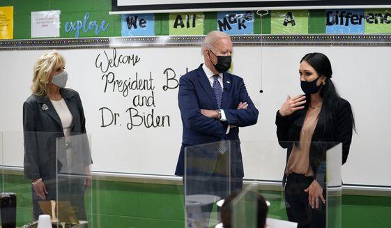 President Joe Biden talks with fifth-grade teacher Cindy Bertamini during a visit to Yorktown Elementary School, Monday, May 3, 2021, in Yorktown, Va., as first lady Jill Biden, looks on. (AP Photo/Evan Vucci)