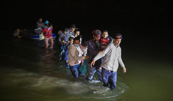 In this March 24, 2021 photo, migrant families, mostly from Central American countries, wade through shallow waters after being delivered by smugglers on small inflatable rafts on U.S. soil in Roma, Texas. (AP Photo/Dario Lopez-Mills) ** FILE **