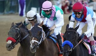 John Velazquez riding Medina Spirit leads Florent Geroux on Mandaloun and Flavien Prat riding Hot Rod Charlie to win the 147th running of the Kentucky Derby at Churchill Downs, Saturday, May 1, 2021, in Louisville, Ky. (AP Photo/Jeff Roberson) **FILE**
