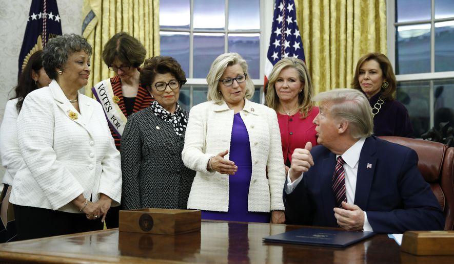 In this Nov. 25, 2019, file photo, Rep. Liz Cheney, R-Wyo., center, speaks with President Donald Trump during a bill signing ceremony for the Women's Suffrage Centennial Commemorative Coin Act in the Oval Office of the White House in Washington. (AP Photo/Patrick Semansky, File)