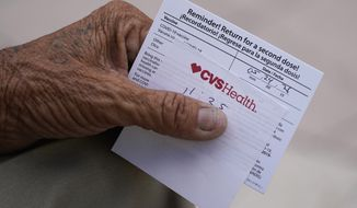 A man holds his vaccination reminder card after having received his first shot at a pop-up vaccination site next to Maximo Gomez Park, also known as Domino Park, Monday, May 3, 2021, in the Little Havana neighborhood of Miami. (AP Photo/Wilfredo Lee)