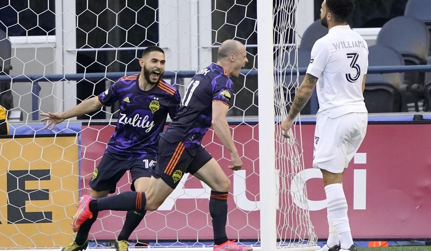 Seattle Sounders' defender Brad Smith, center, celebrates with midfielder Alex Roldan, left, as Los Angeles Galaxy's defender Derrick Williams looks on after Smith scored a goal during the first half of an MLS soccer match, Sunday, May 2, 2021, in Seattle. The Sounders won 3-0. (AP Photo/Ted S. Warren)