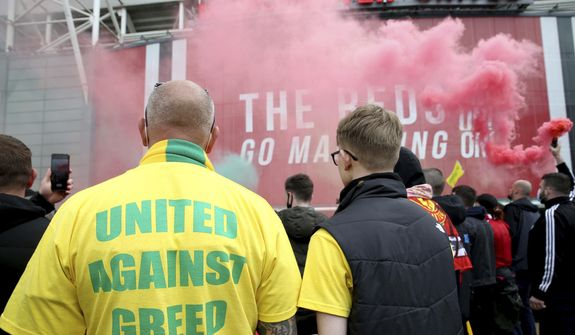 """A fan wears a shirt with a """"United Against Greed"""" message, as fans gather to protest against the Glazer family, the owners of Manchester United, outside Old Trafford stadium, in Manchester, England, before their English Premier League match against Liverpool, Sunday, May 2, 2021. Manchester United supporters have stormed into the stadium and onto the pitch ahead of Sunday's game against Liverpool as fans gathered outside Old Trafford to protest against the Glazer ownership. (Barrington Coombs/PA via AP) **FILE**"""