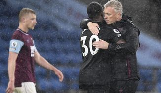 West Ham's manager David Moyes, right, hugs West Ham's Michail Antonio on the pitch after the end of the English Premier League soccer match between Burnley and West Ham United and at Turf Moor stadium in Burnley, England, Monday, May 3, 2021. West Ham won the game 2-1 with West Ham's Michail Antonio scoring both of their goals. (AP Photo/Peter Powell/Pool via AP)