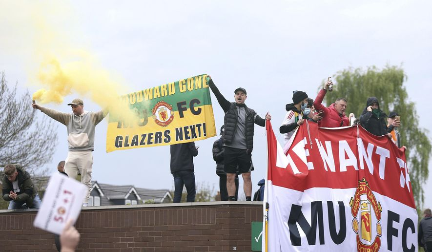 Fans hold up banners as they protest against the Glazer family, owners of Manchester United, before their Premier League match against Liverpool at Old Trafford, Manchester, England, Sunday, May 2, 2021. (Barrington Coombs/PA via AP)
